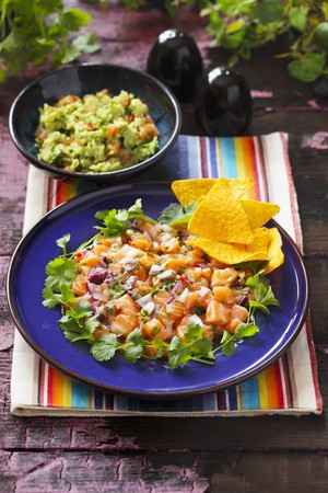 main course: Ceviche as a main course on a blue plate with coriander and tortilla chips and a bowl of guacamole in the background