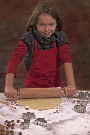 worktops: A girl rolling out biscuit dough with a rolling pin on a work surface LANG_EVOIMAGES