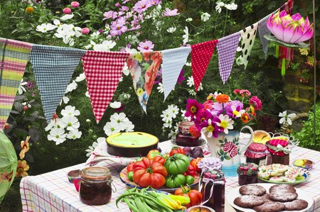 festoons: A table laid in a garden with biscuits, fresh vegetables, jam and cake