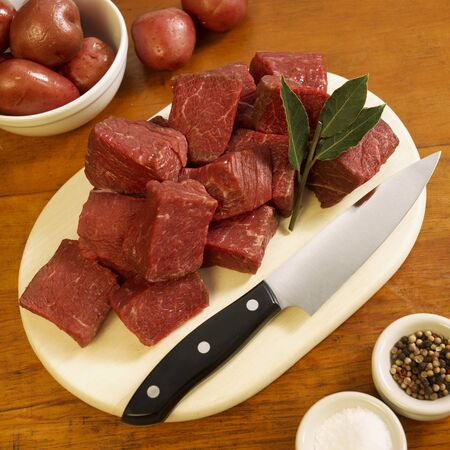 cubed: Cubed Grass Fed Beef Sirloin Tips on Cutting Board; Peppercorns, Salt and Red Potatoes