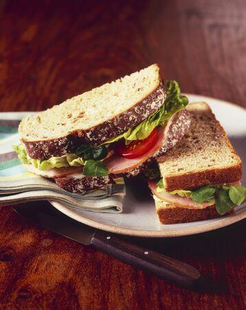 ham sandwich: Panino al prosciutto con lattuga e pomodoro su pane di frumento; Dimezzato su una piastra LANG_EVOIMAGES