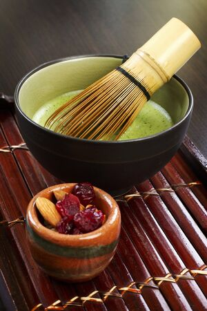 vaccinium macrocarpon: Matcha tea with a tea whisk and almonds and dried cranberries LANG_EVOIMAGES