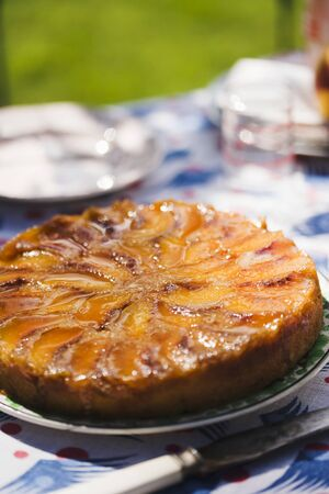 turned out: Whole Peach Upside Down Cake on a Sunny Outdoor Table