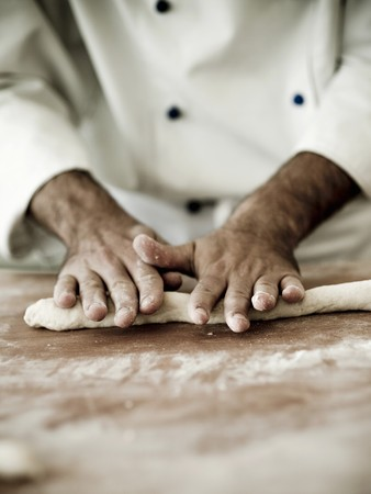 solo form: A chef rolling out gnocchi dough on a floured work surface