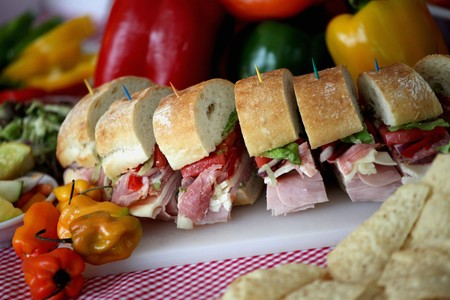 hero sandwich: Party Sub Sliced with Toothpicks; On a Cutting Board; Peppers and Chips