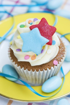 childs birthday party: A vanilla cupcake with colourful stars, sugar confetti and blue sugared almonds