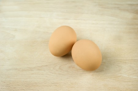 brownness: Two fresh eggs on a wooden surface