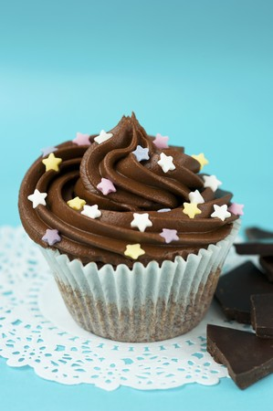 doiley: A cupcake with chocolate icing and sugar stars in a paper case on a doily, and pieces of chocolate