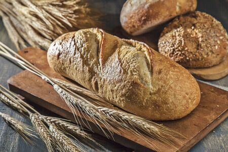 several breads: Assorted Loaves of Bread with Wheat Stalks LANG_EVOIMAGES