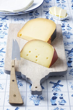 delftware: Dutch cheeses (Leerdammer, Old Amsterdam) on a board on a Dutch tablecloth LANG_EVOIMAGES