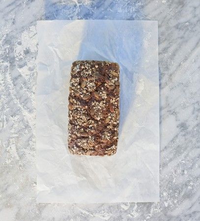 multi grain sandwich: A tin-baked loaf topped with rolled oats, pumpkin seeds and sunflower seeds, on paper, on a marble slab dusted with flour
