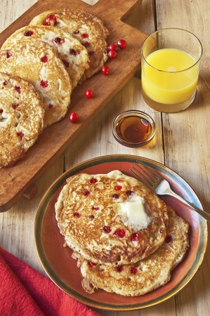 vaccinium macrocarpon: Cranberry Pancakes on a Plate and Cutting Board; Glass of Orange Juice and Maple Syrup