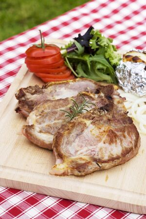 qs: Grilled pork chops with sides on a chopping board LANG_EVOIMAGES