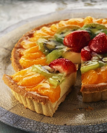 kiwis: Fruit tart topped with mandarins and strawberries, with one slice cut
