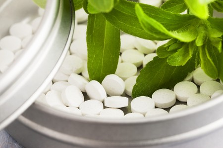 sweetening: Stevia plant leaves and stevia tablets in a small tin