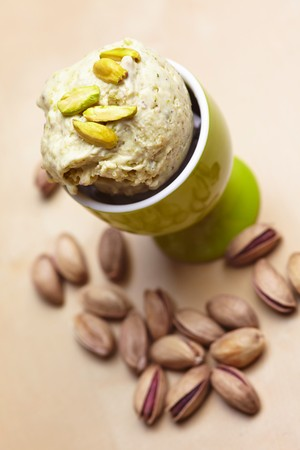 eggcup: Pistachios in an eggcup with roasted pistachios to one side
