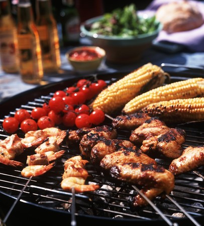 prawn skewers: Chicken wings, prawn skewers, baby sweetcorn and tomatoes on the barbecue grill