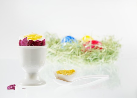 beheaded: A boiled egg with the top cut off, in an eggcup, with an Easter nest of colourful eggs in the background