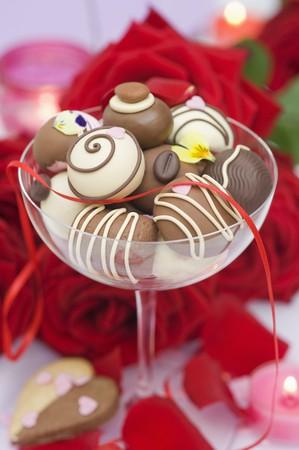 roses rouges: Bonbons au chocolat assortis dans un verre de champagne, des roses rouges