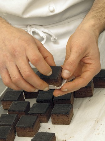 being the case: Chocolate cubes being placed into praline cases LANG_EVOIMAGES