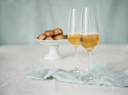 champers: Two Glasses of Champagne with a Pedestal Dish of Macaroons in the Background