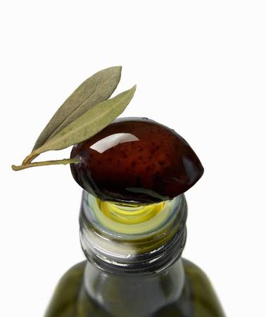 oil bottle: A black olive on top of an olive oil bottle