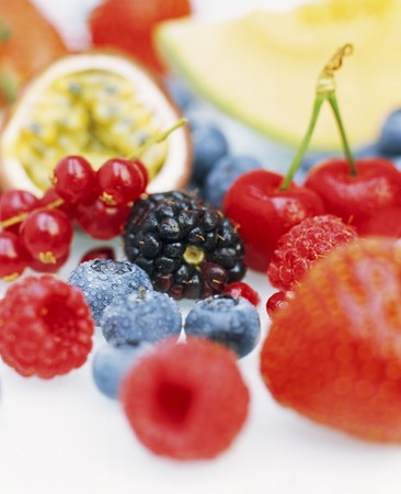 Close up of a selection of fresh fruits including blueberries, redcurrants, passion fruit, raspberries, blackberries, strawberries and cherries.
