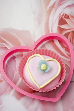 plastic heart: close up di una rosa ghiacciato, amore cuore a forma di torta tazza con un cutter a forma di cuore biscotti di plastica rosa