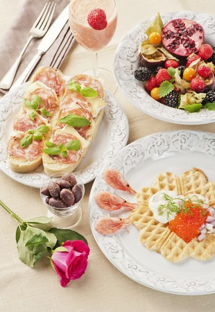 A breakfast of a caviar-topped waffle, slices of bread topped with cheese and ham, fresh fruits and a strawberry and mango smoothie LANG_EVOIMAGES