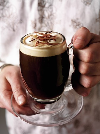 hold ups: Hands holding a glass mug of Irish coffee LANG_EVOIMAGES