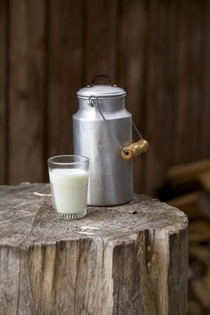melk glas: Een melkbus en een glas melk op een rustieke houten blok
