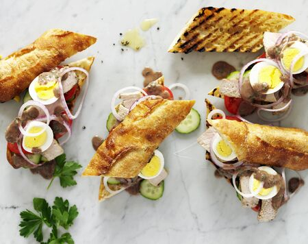 several breads: Egg and Roast Beef Sandwiches on Grilled Baguettes with Onions, Parsley BBQ Sauce and Cucumbers LANG_EVOIMAGES