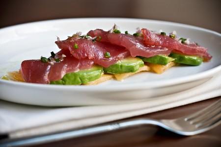 tunafish: Raw Tuna Slices Over Sliced Avocado on a White Plate