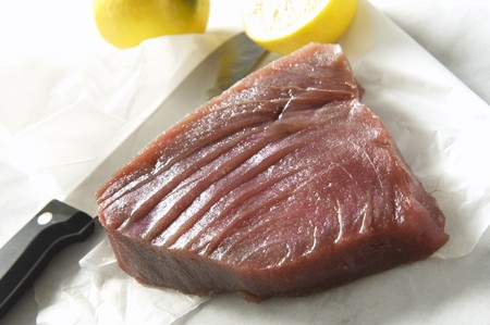 tunafish: Raw tuna with a knife and lemons LANG_EVOIMAGES