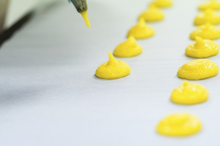 piped: Mixture for yellow macaroons being piped onto grease-proof paper
