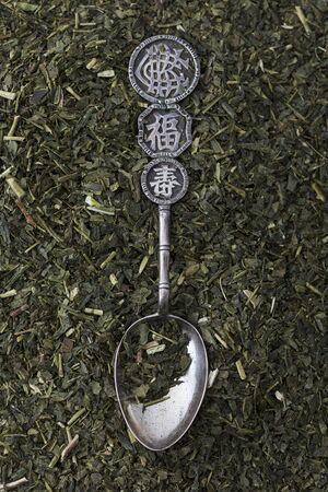 sencha tea: An Oriental silver spoon lying on sencha tea leaves
