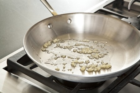 producing: Sauteing Minced Garlic in a Skillet with Olive Oil LANG_EVOIMAGES
