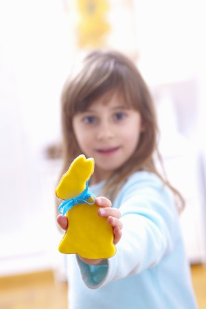 10 to 12 year olds: A girl holding a biscuits in the shape of an Easter bunny with yellow icing
