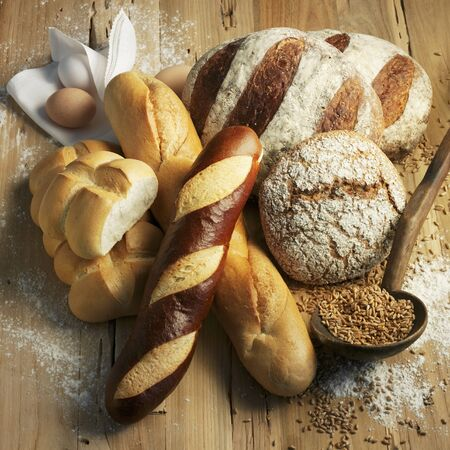 several breads: Assorted types of bread on a wooden surface LANG_EVOIMAGES