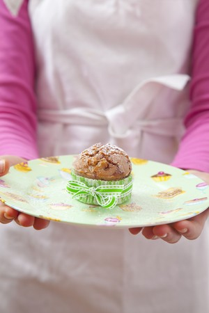 10 to 12 year olds: A girl holding a raspberry muffin dusted with icing sugar LANG_EVOIMAGES