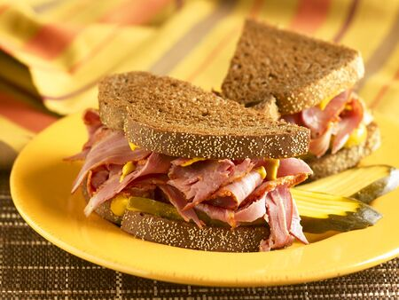 pumpernickel: Corned Beef Sandwich with Mustard and Pickles on Pumpernickel Bread; Halved on a Yellow Plate LANG_EVOIMAGES
