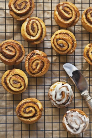 cinammon: Cinnamon Buns on a Cooling Rack with Vanilla Icing