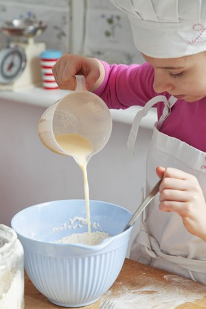 12 step: A girl pouring milk into a bowl of flour