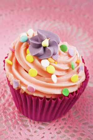 buttercream: A cupcake decorated with buttercream, sugar sprinkles and a sugar flower
