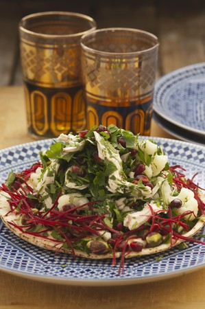 moroccan cuisine: Chicken salad with parsley and pomegranate seeds on unleavened bread