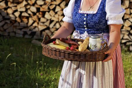 farmyards: A woman wearing a dirndl and carrying a tray holding a light meal
