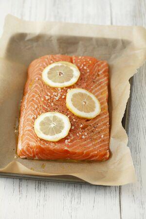 lemon slices: Filetto di salmone con sale, pepe e fette di limone