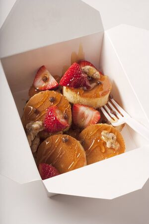 take out: Mini Pancakes with Strawberries, Nuts and Honey in a Take Out Container