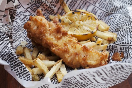 uk cuisine: Fish and Chips with Lemon on Newspaper LANG_EVOIMAGES