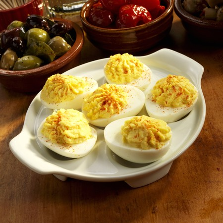 deviled eggs: Dish of Deviled Eggs with Olives and Peppers in the Background LANG_EVOIMAGES